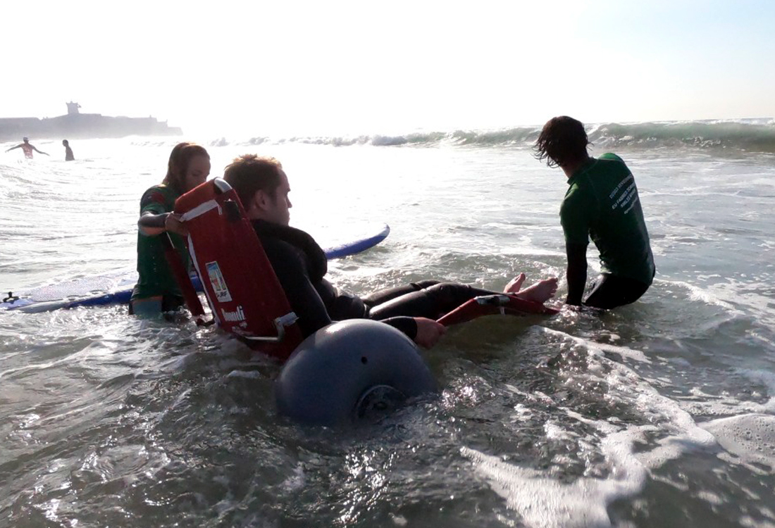 FFALP class of 2019 at surfing session with participant being transferred from a beach wheelchair to a surf board, with the support of two volunteers