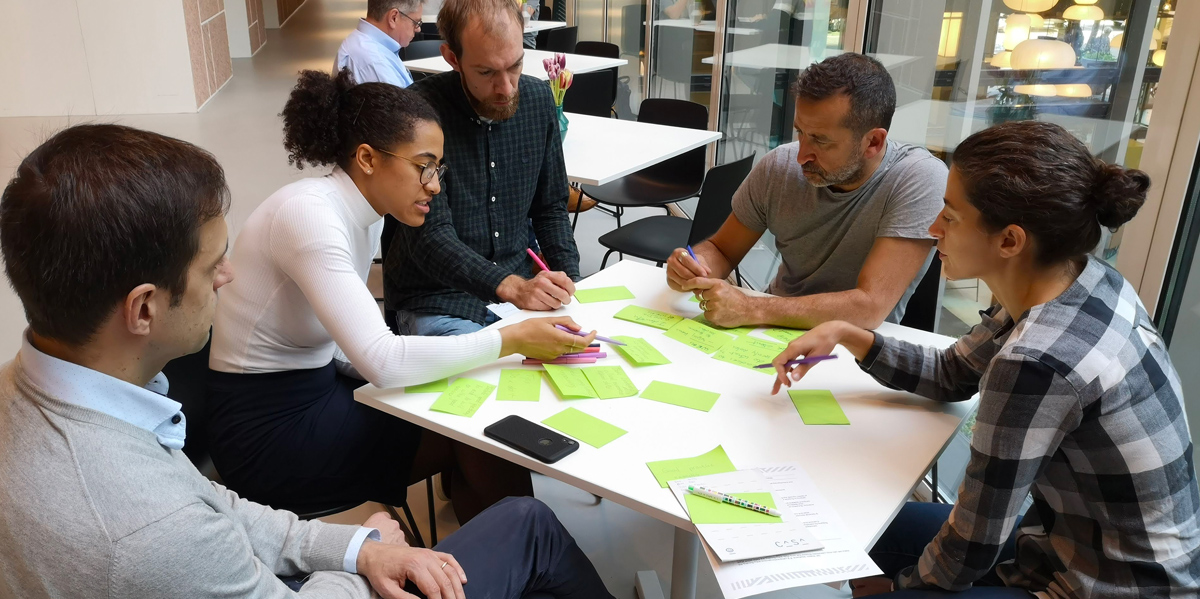 Innovating Football Leadership through Practice and Policy group brainstorming at a table writing on post-its