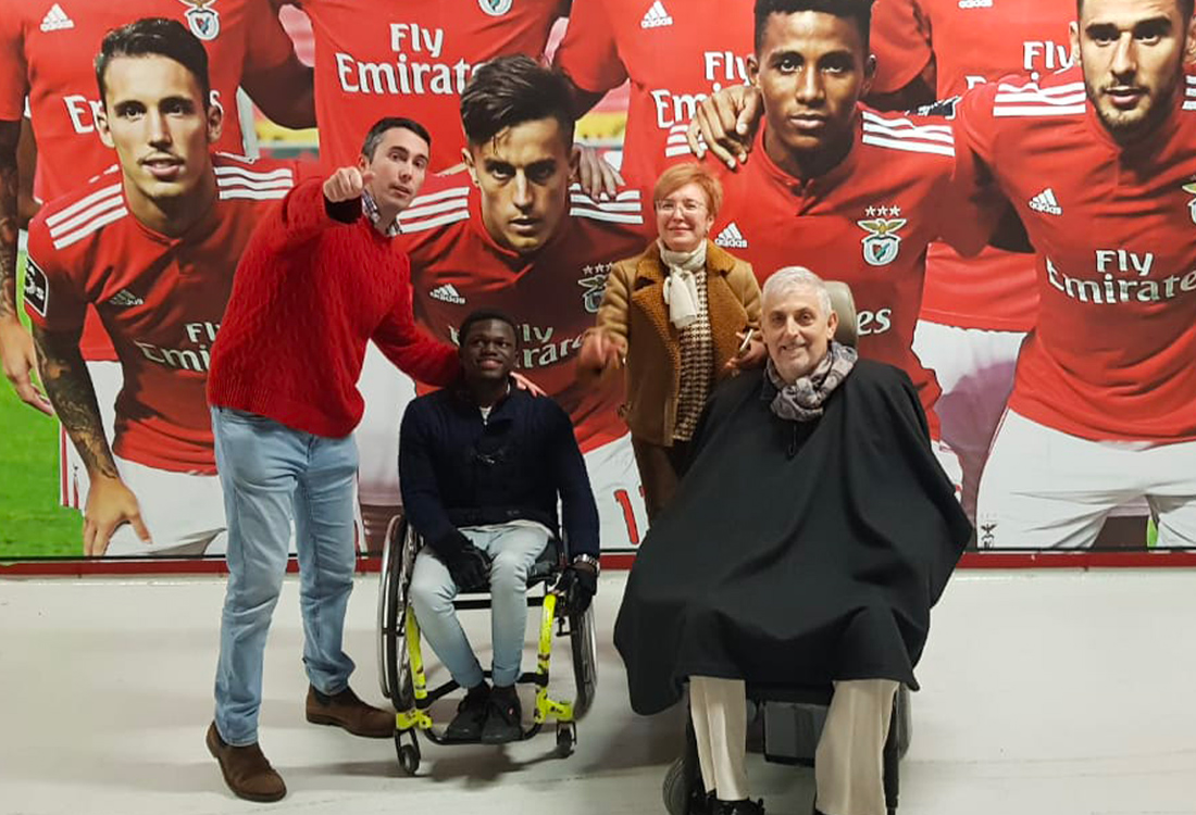 Football For All Leadership Programme participants at SL Benfica Stadium with José Soares and a background picture of Benfica players