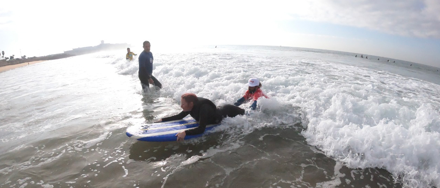 Football For All Leadership Programme participant at an adapted surf session, on a surf board with a volunteer supporting her
